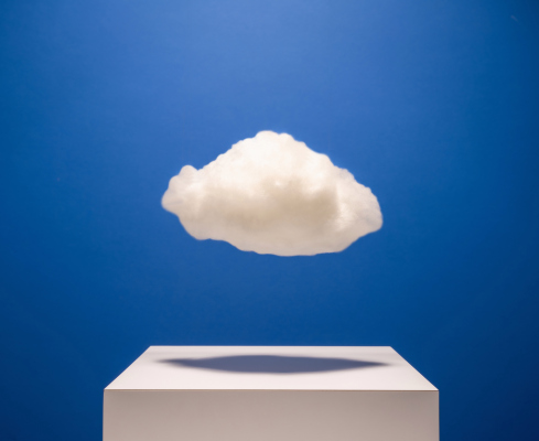 White cloud hovering over white surface with drop shadow on blue background, studio shot