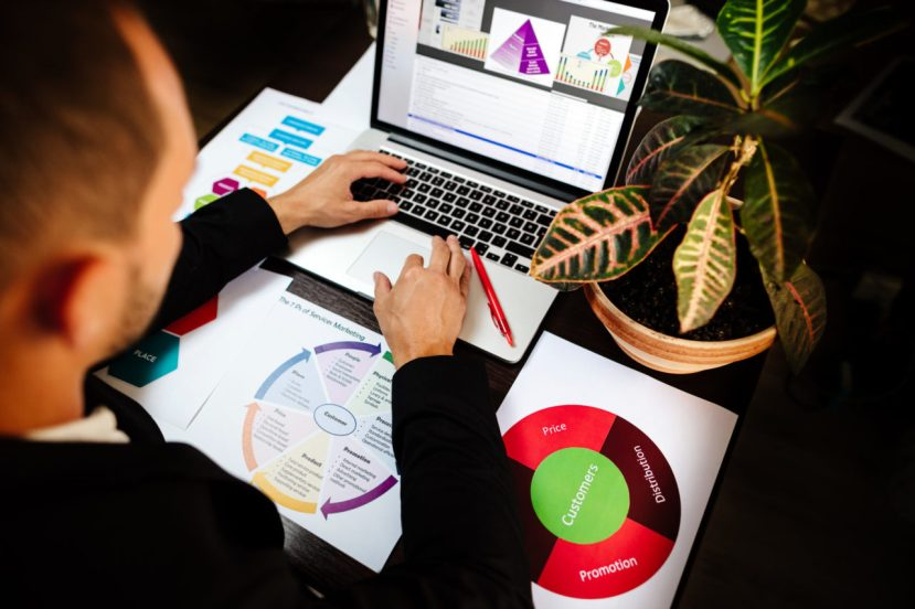 marketing product manager holding marketing promotion plan marketing product manager desk. Marketing mix plan for target market.