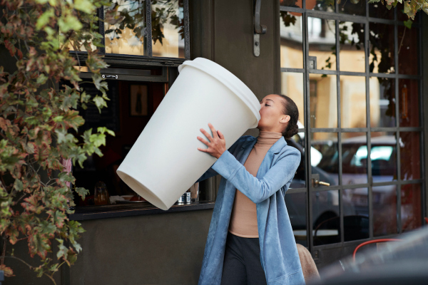 Young woman drinking coffee from large disposable cup at take away counter of cafe