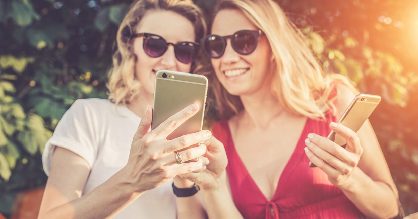 Sunny summer day. Close-up of a smartphone in the hands of young women standing outdoors. Girl in white t-shirt shows a picture on the screen of the smartphone girl in a red dress. Girls using gadget